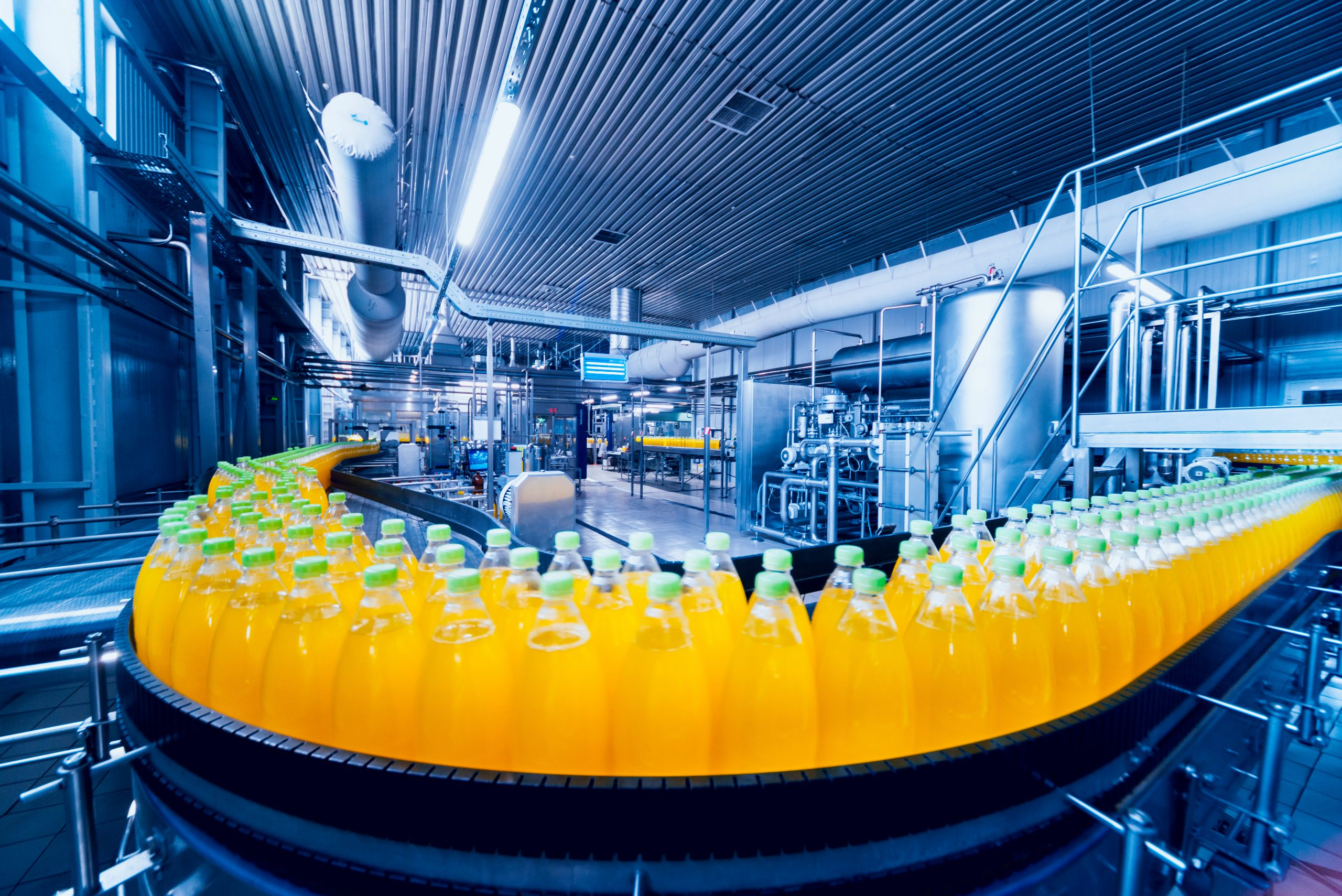 a line of juice bottles are created on an assembly line